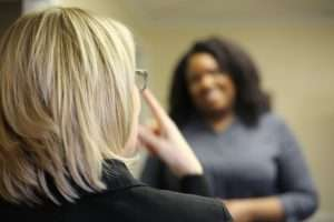 interpreter with light blonde hair and glasses signing to an african-american client.
