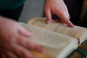 A book being held open with a person's blurred right hand while the focus is on the person's left hand following the words.