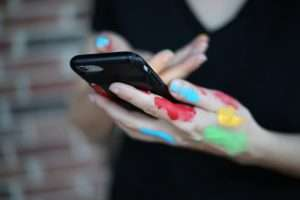 A woman from the neck down is holding an iPhone with one painted hand while gesturing to the screen with the other.