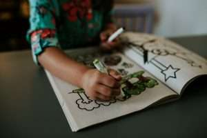 Child from the neck down, sitting at a table, coloring a coloring book with images of trees, and using a green marker.
