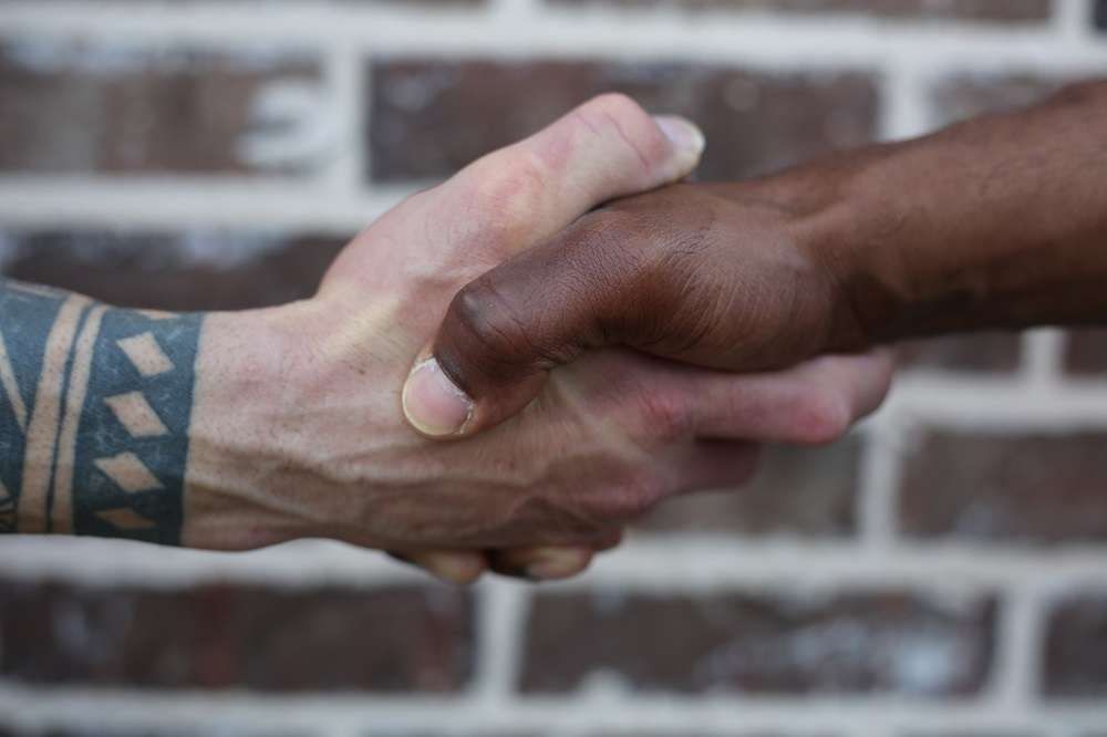 Up-close handshake of a man with light skin and tattoos and a man with dark skin. Blurs to a red brick wall background.