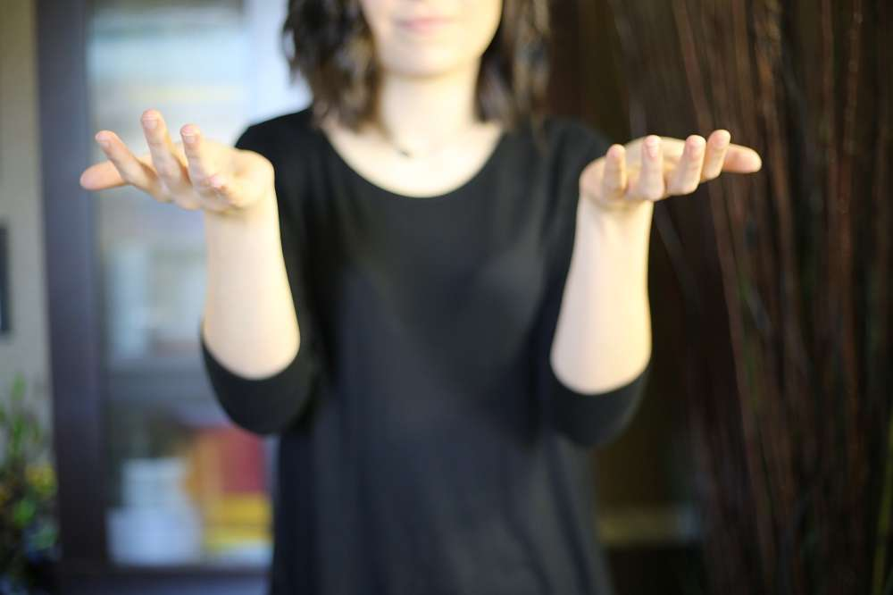 "A blurred woman from the nose down, wearing black. Her hands are held at shoulder height with palms up signing ""why""."
